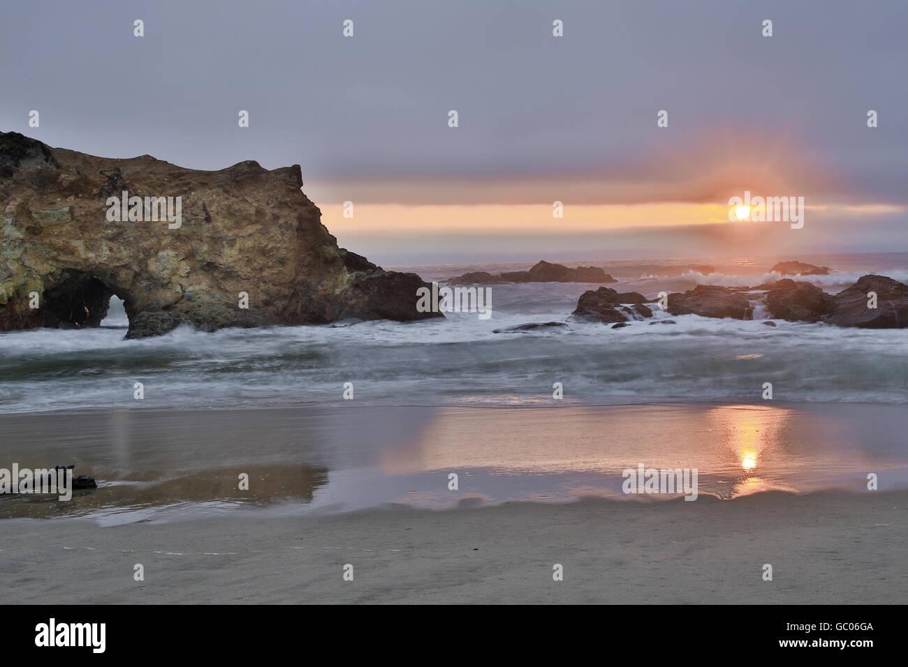 Sun shines through overcast sky in Pescadero State Beach. - Stock Image
