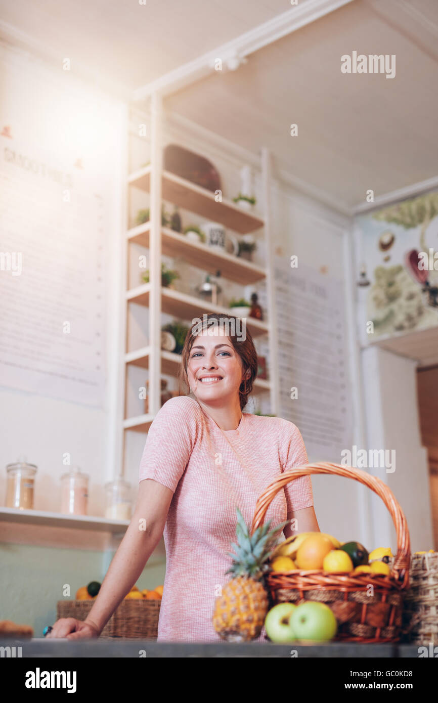 Smiling juice bar owner standing behind the counter and looking at camera. Caucasian young woman working in juice - Stock Image