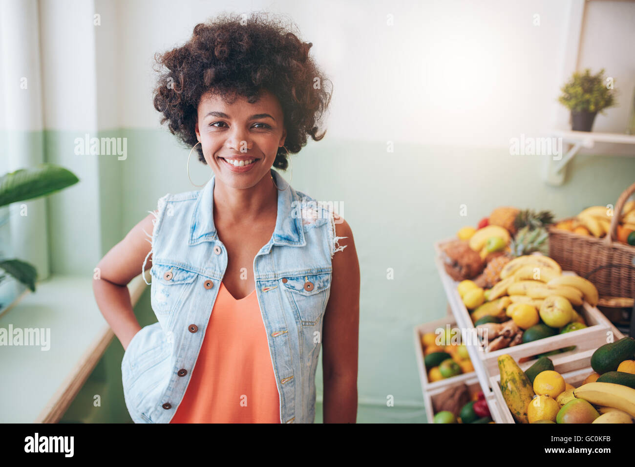 Portrait of happy young juice bar owner looking at camera