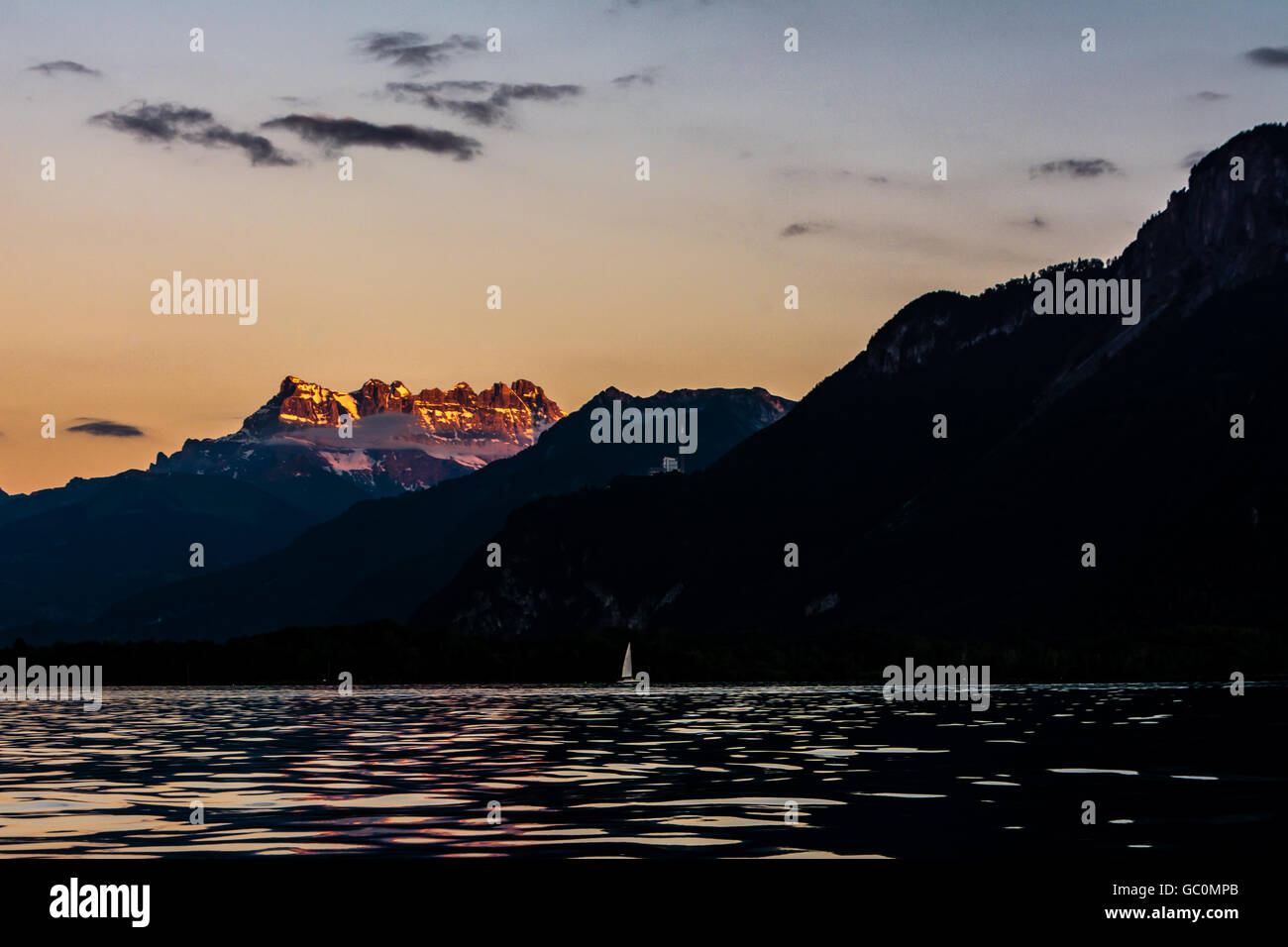 A single boat on Lake Geneva in Switzerland at sunset in summer with the Dents du Midi mountain range lit by the - Stock Image