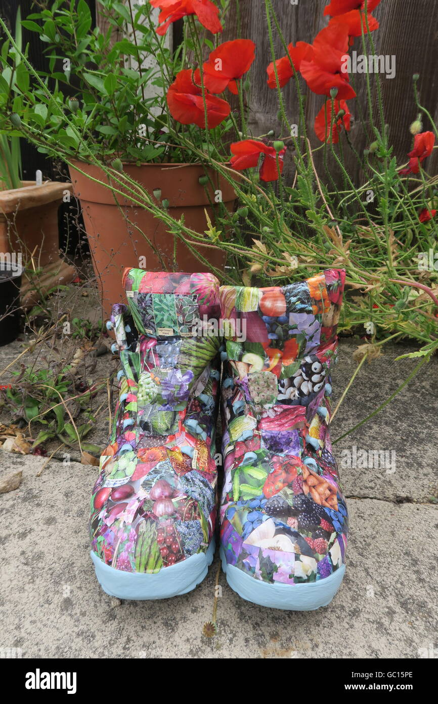 Walking boots, re-purposed as garden containers and decorated with images from a gardening catalogue, using decoupage Stock Photo