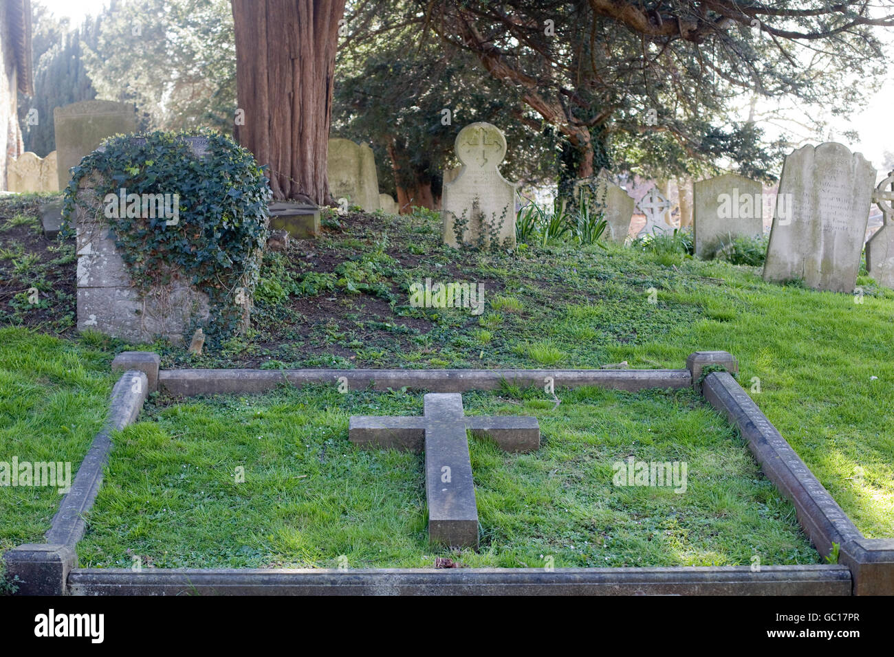 stone cross on a grave - Stock Image