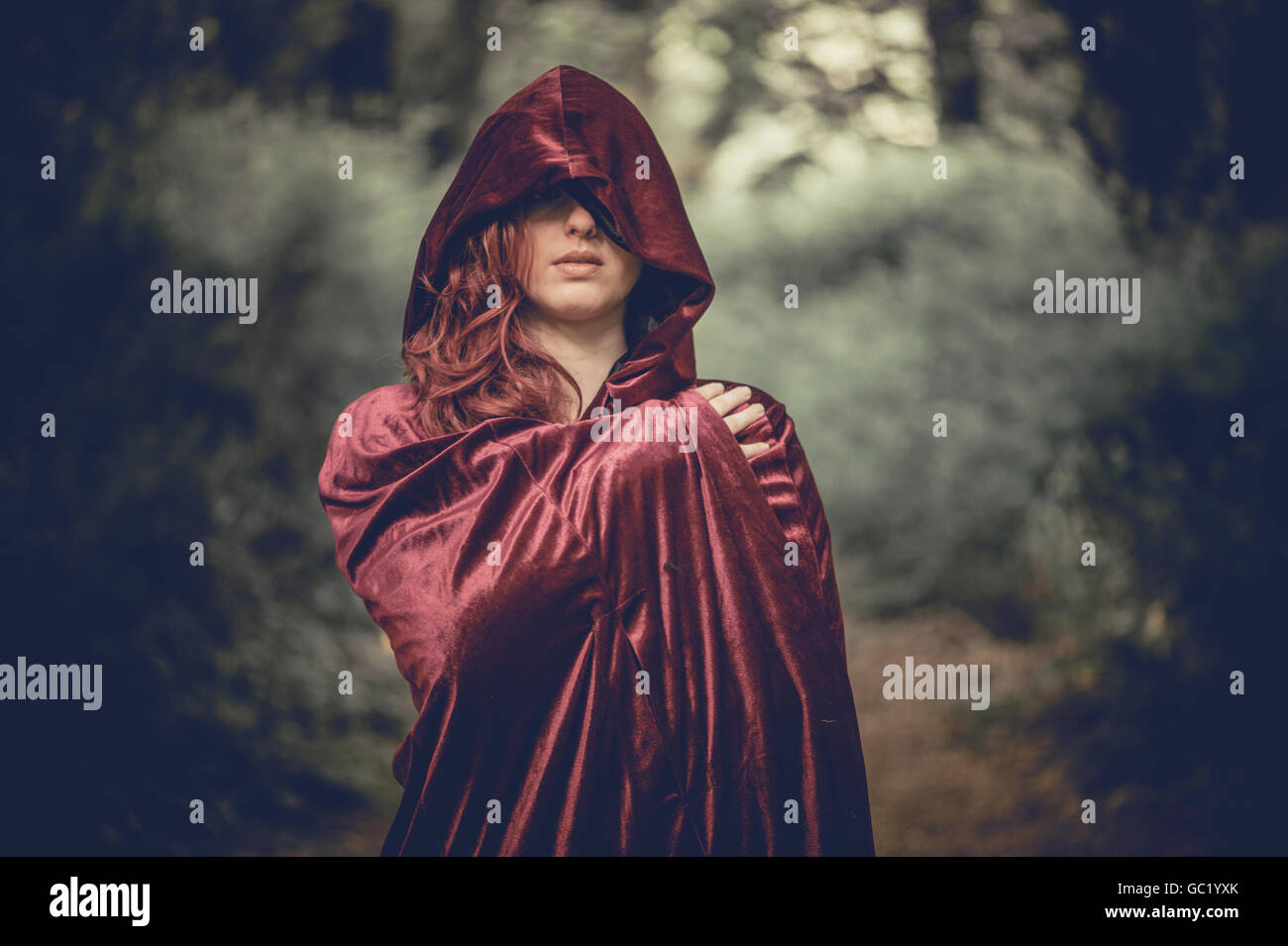 Woman of mystery: A young red haired redhead woman girl wearing a cape, obscuring her face, alone in a forest, looking - Stock Image