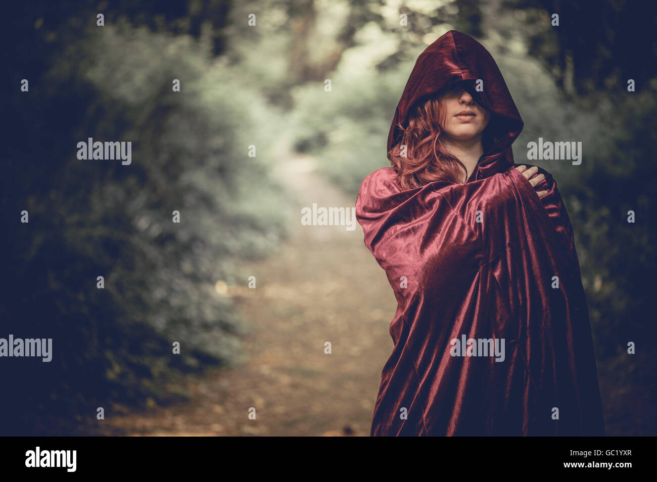 Woman of mystery: A young red haired redhead woman girl wearing a cape, obscuring her face, alone in a forest - Stock Image