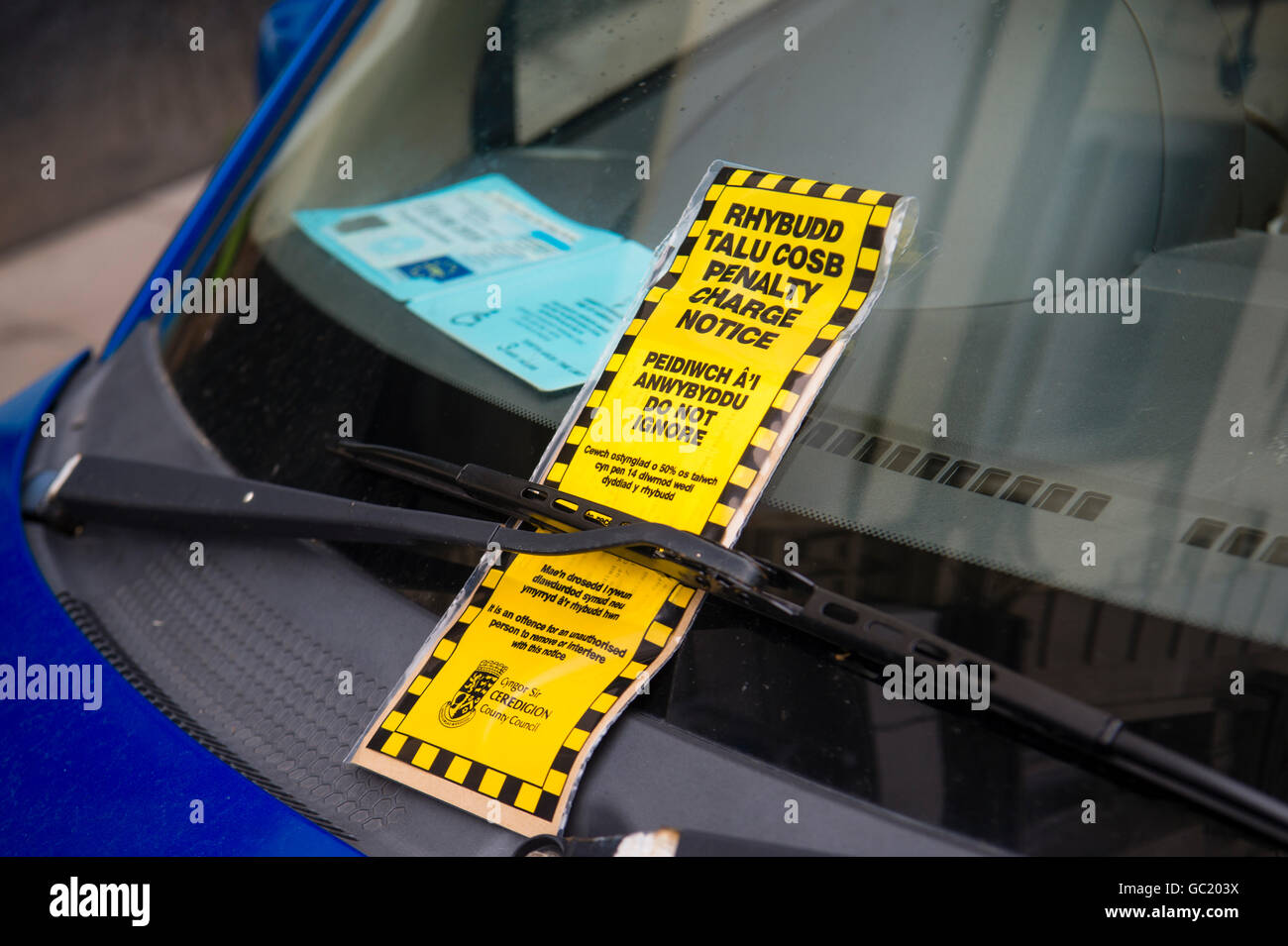 A car parking fixed penalty notice  ticket, in welsh and english language, on the windscreen of a car which also - Stock Image