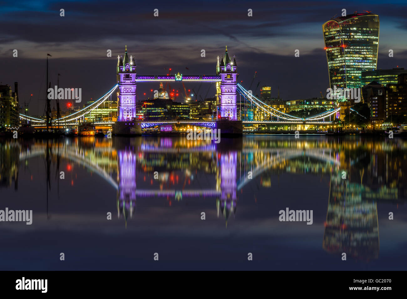 Illuminated London cityscape with Tower Bridge and Fenchurch building at sunset - Stock Image