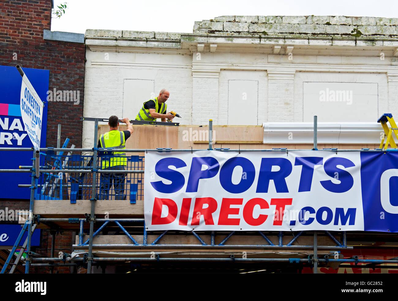 Workmen renovating Sports Direct store in Oswestry, Shropshire, England UK - Stock Image