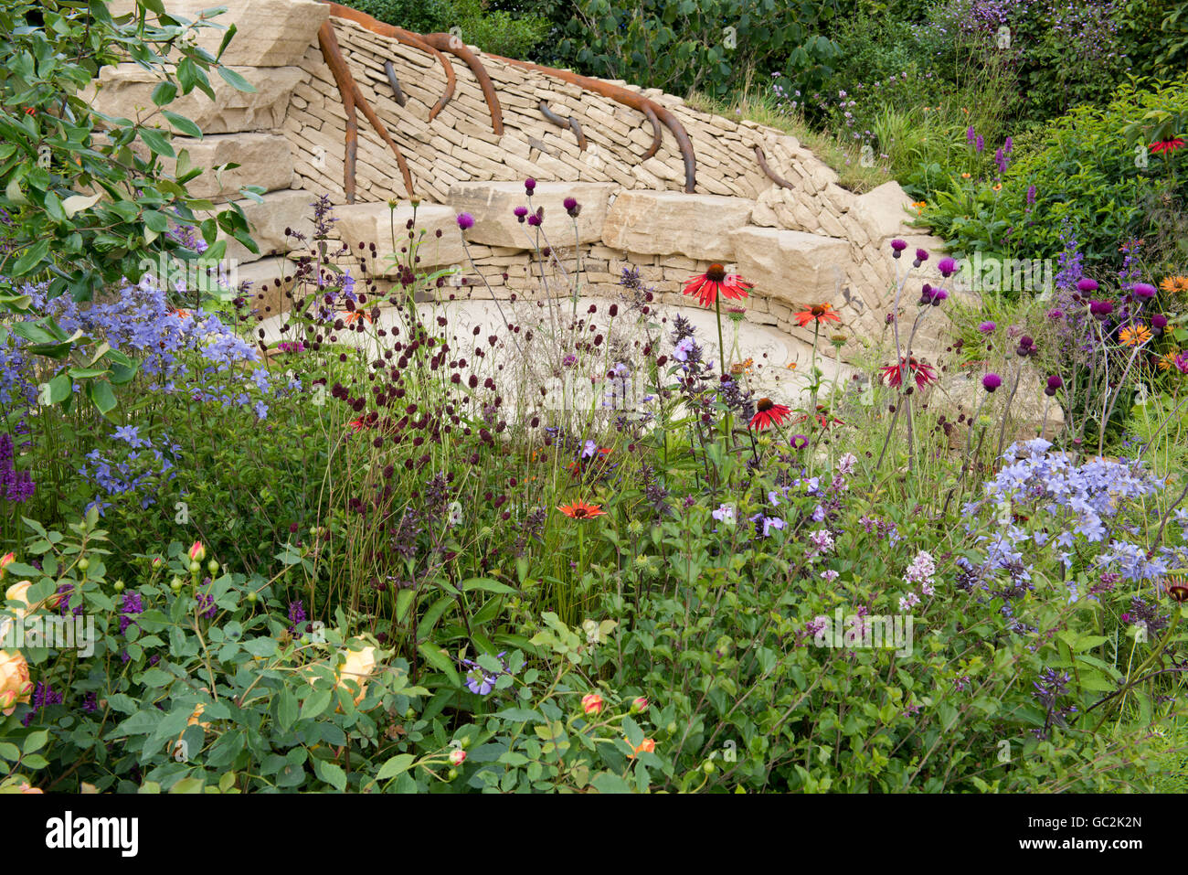 A stone seating area surrounded by naturalistic planting in The Zooflora: Outstanding Natural Beauty Garden - Stock Image