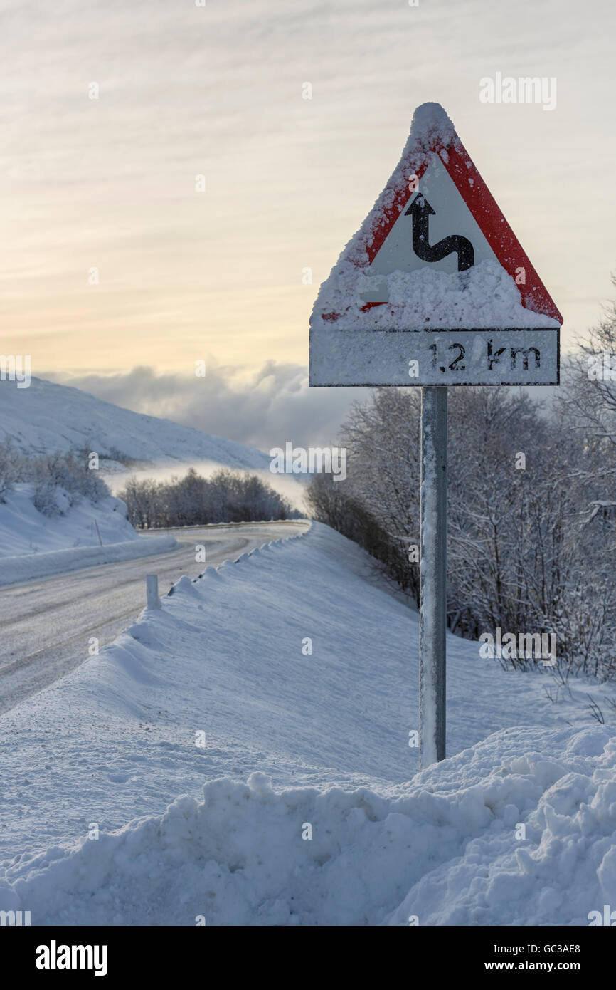 Wintry road with warning sign, European route E10, winding route, Hinnøya Island, Nordland, Norway - Stock Image