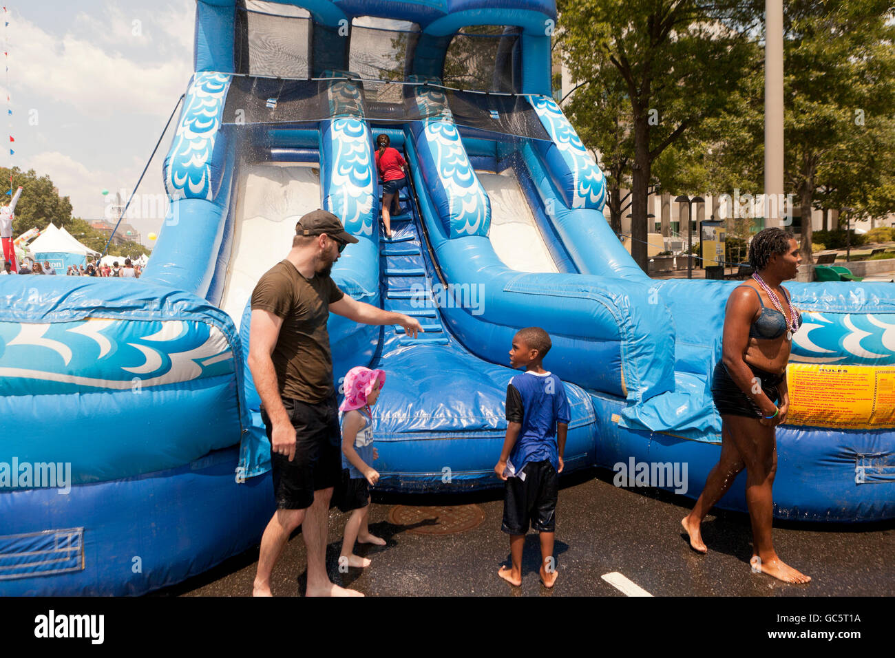 Inflatable water slide at an outdoor event - USA - Stock Image