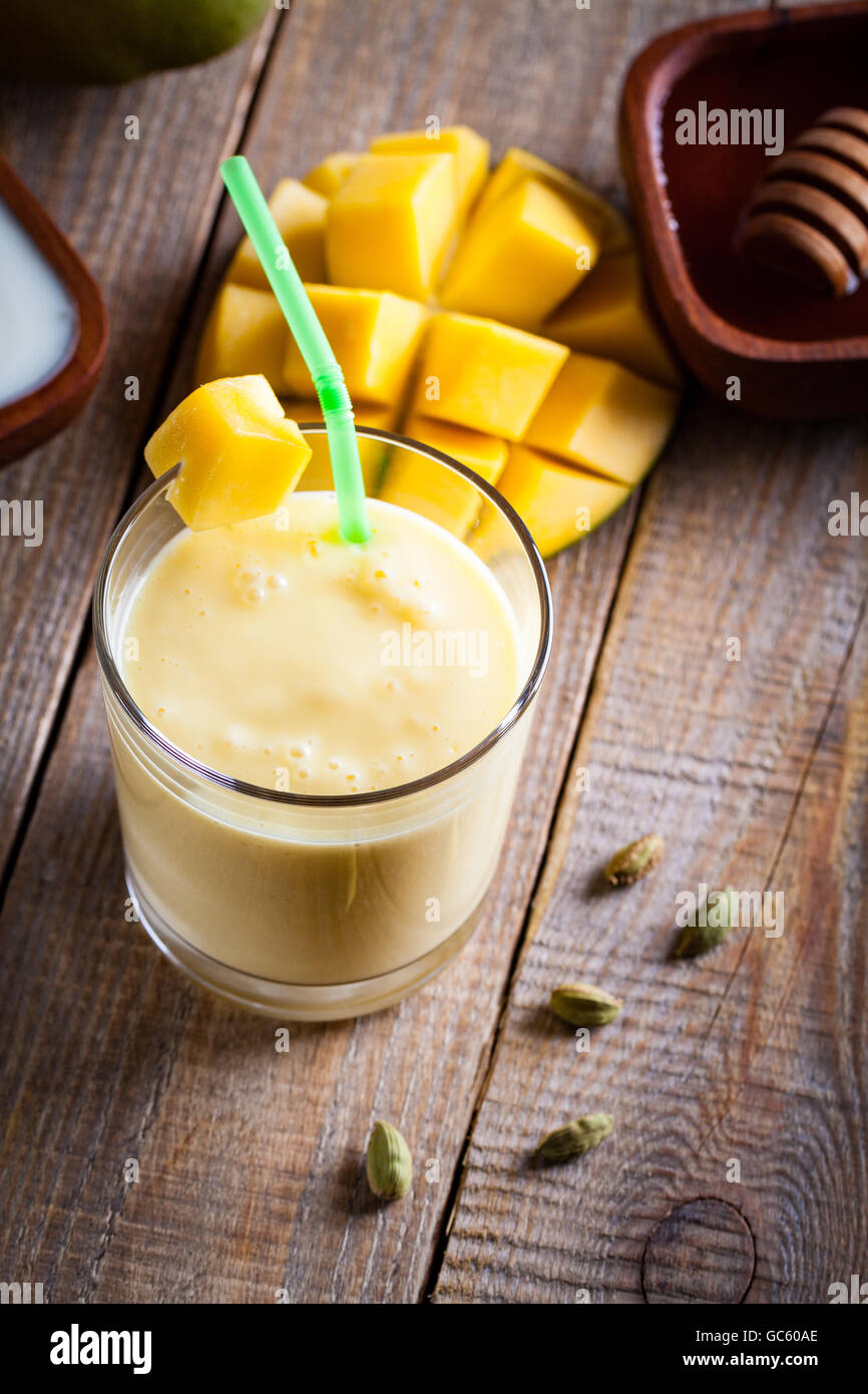 Glass of mango lassi Indian drink flavored with cardamom. Milkshake on wooden background. - Stock Image