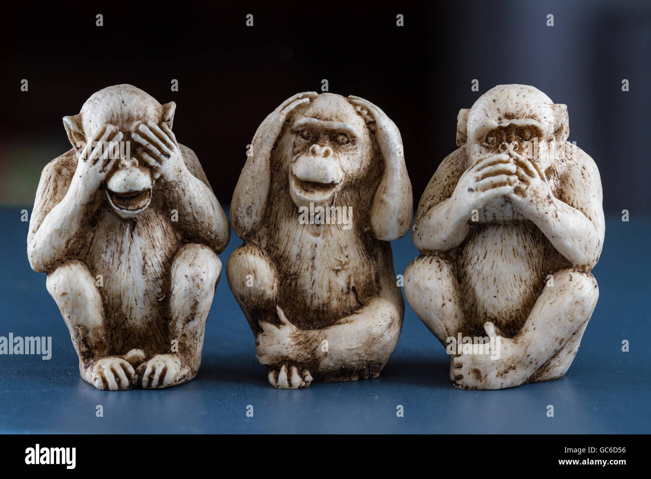 close up of hand small statues with the concept of see no evil, hear no evil and speak no evil. - Stock Image