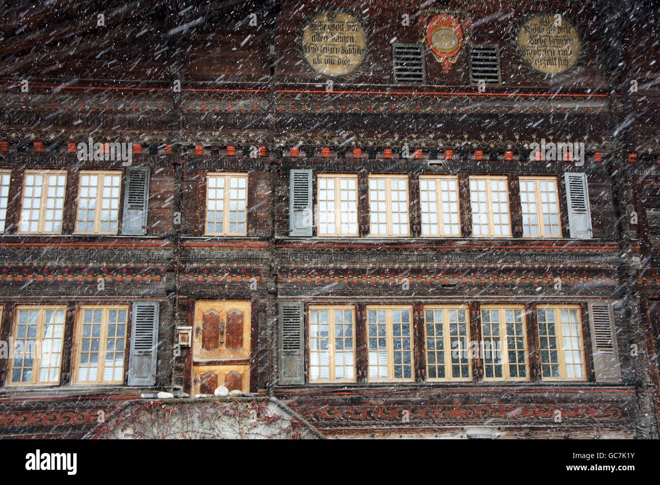 "The ""Stucki houise"" a decorated historic log house in Bernese traditional style  with snow, Reichenbach, Switzerland Stock Photo"