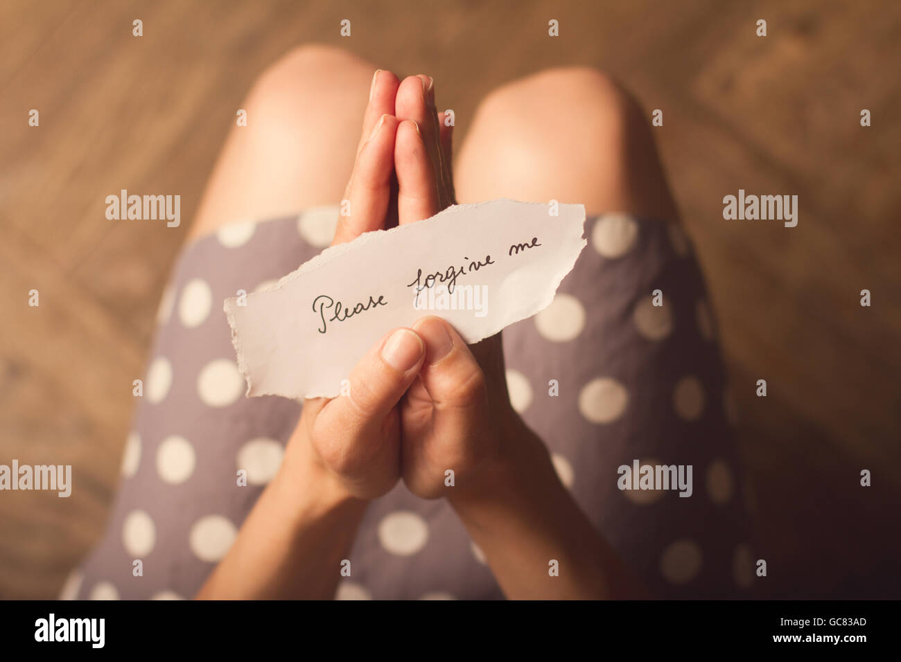 Top view of woman in dotted dress holding a paper message with the text please forgive me - Stock Image