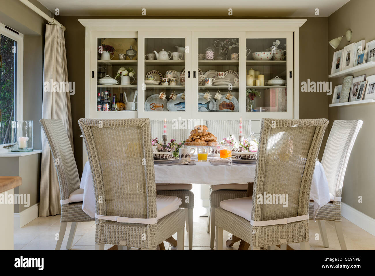 Fulham Lloyd Loom dining chairs around table laid with croissant. A large white dresser stands in the background - Stock Image