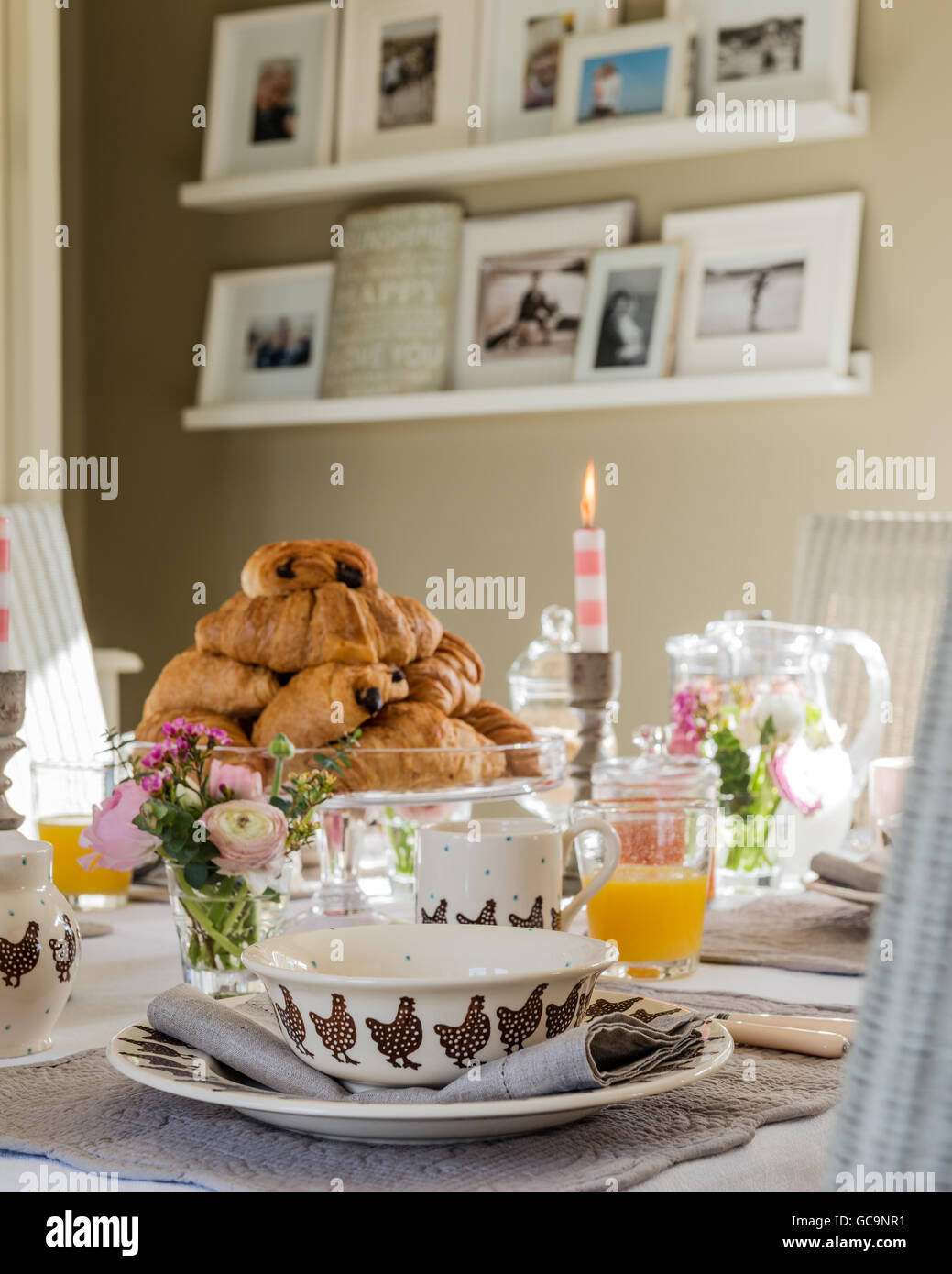 Pile of pain au chocolate on table laid for breakfast. Floating shelves are on the wall in the background displaying - Stock Image