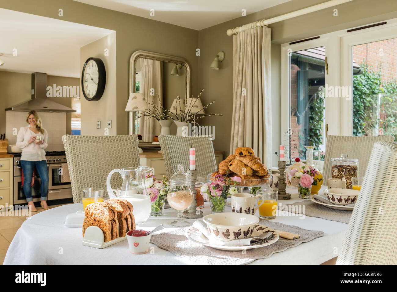 Table laid with breakfast croissant and toast. The dining chairs are Fulham Lloyd and Loom. - Stock Image