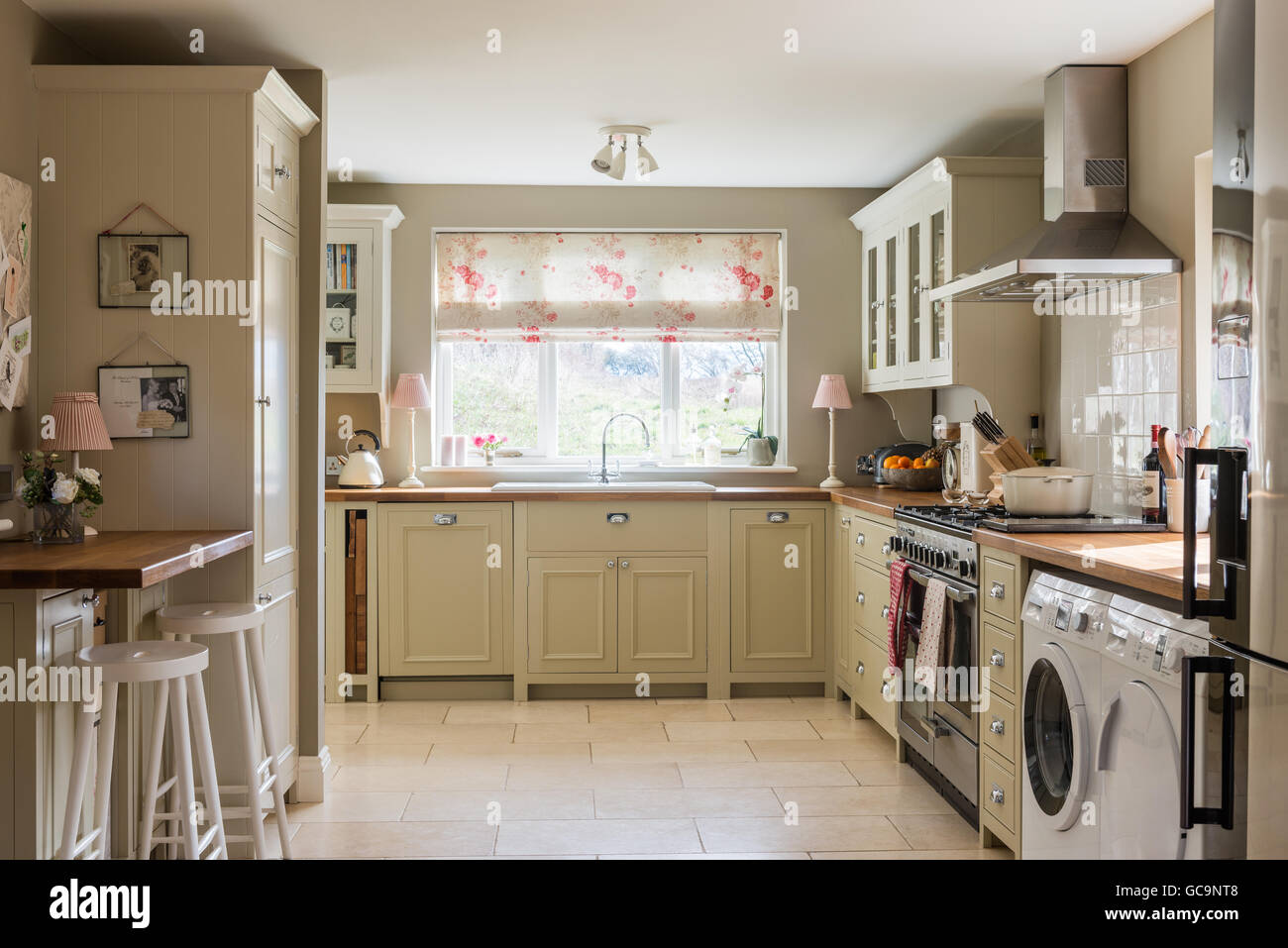 Country style kitchen with units from Neptune and tumbled limestone floor tiles. The Roman blind is made up in Kate - Stock Image