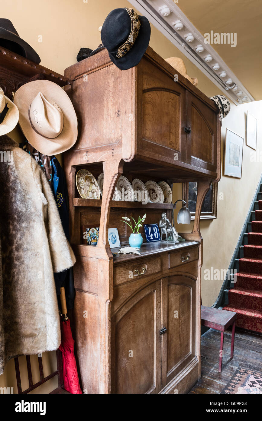 Antique wooden cabinet with hats and coats in Nottinghill hallway, London, UK - Stock Image