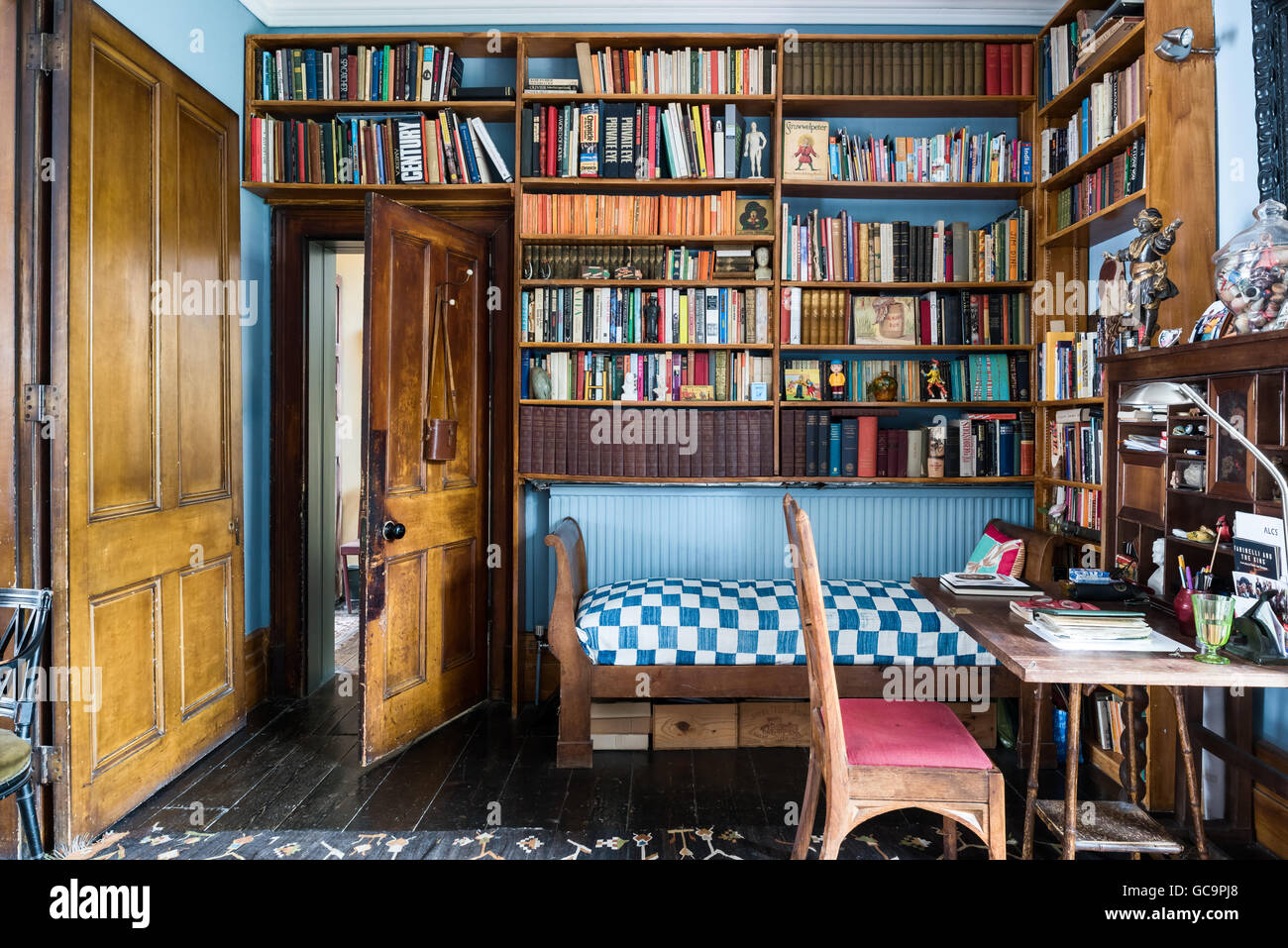Wooden bookshelves above daybed with desk in study of Nottinghill home, London, UK - Stock Image