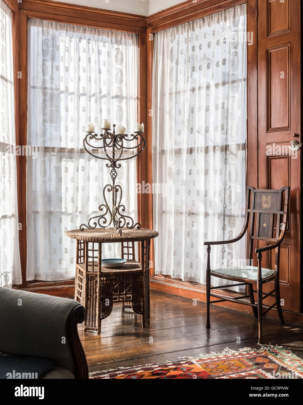 Metal candlestick on wicker side table in window of Nottinghill Victorian terrace, London, UK - Stock Image