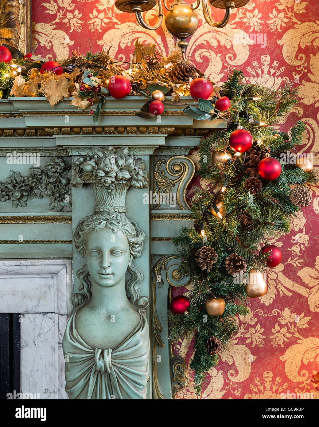 Red and gold damask wallpaper with bauble garland on fireplace in dining room of Grade I listed, Victorian Gothic - Stock Image