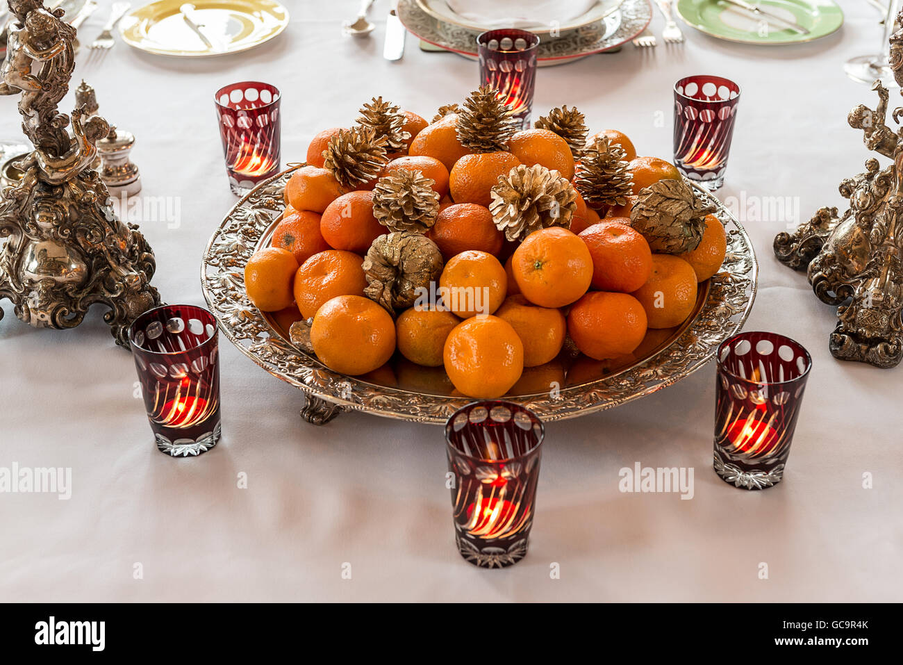 Satsumas and pinecones with lit tealight holders on dining table in Grade I listed, Victorian Gothic Carlton Towers, - Stock Image