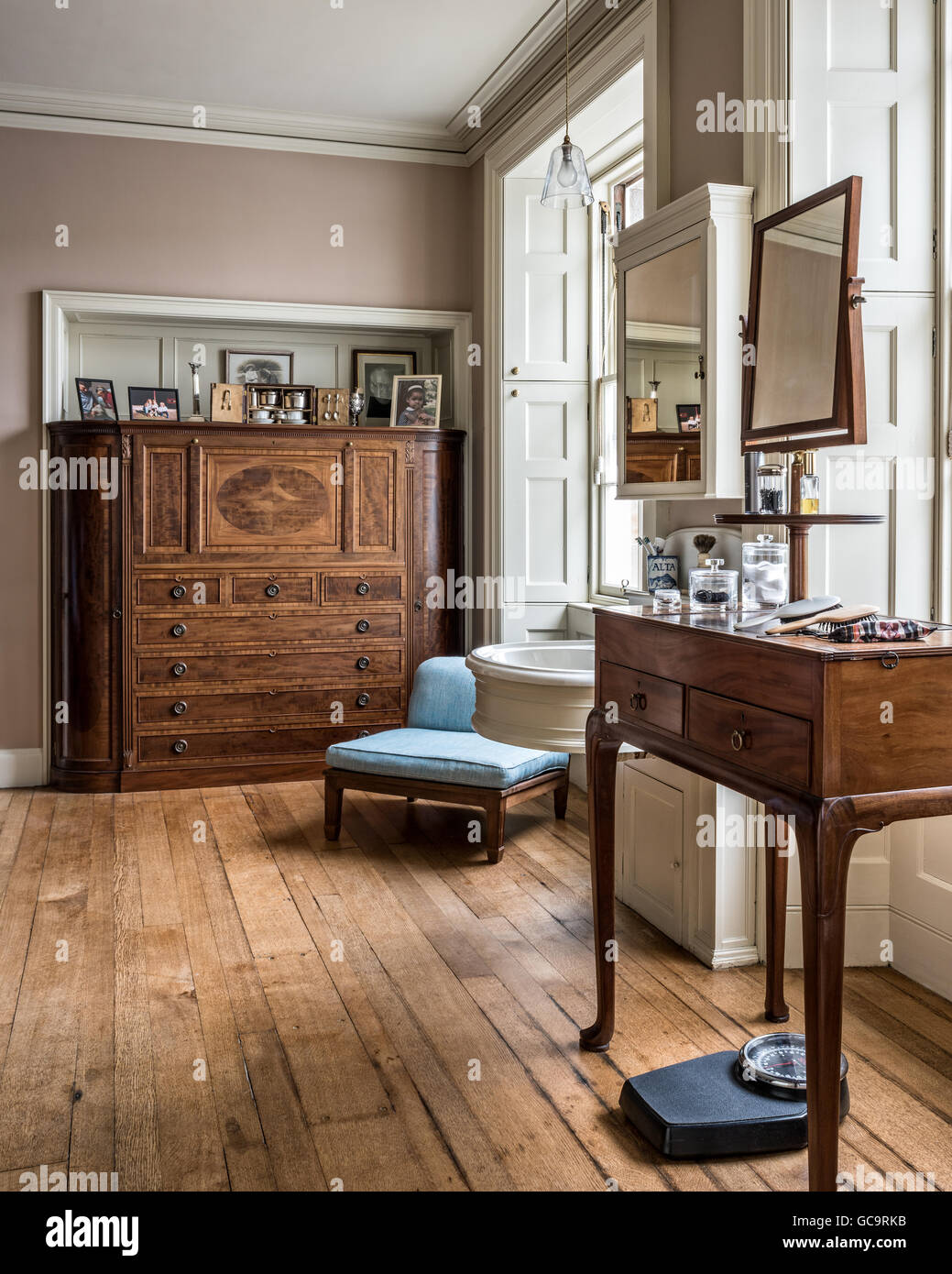Porcelain hand-basin and a Whytock and Reid dressing chest in a spacious dressing room. - Stock Image