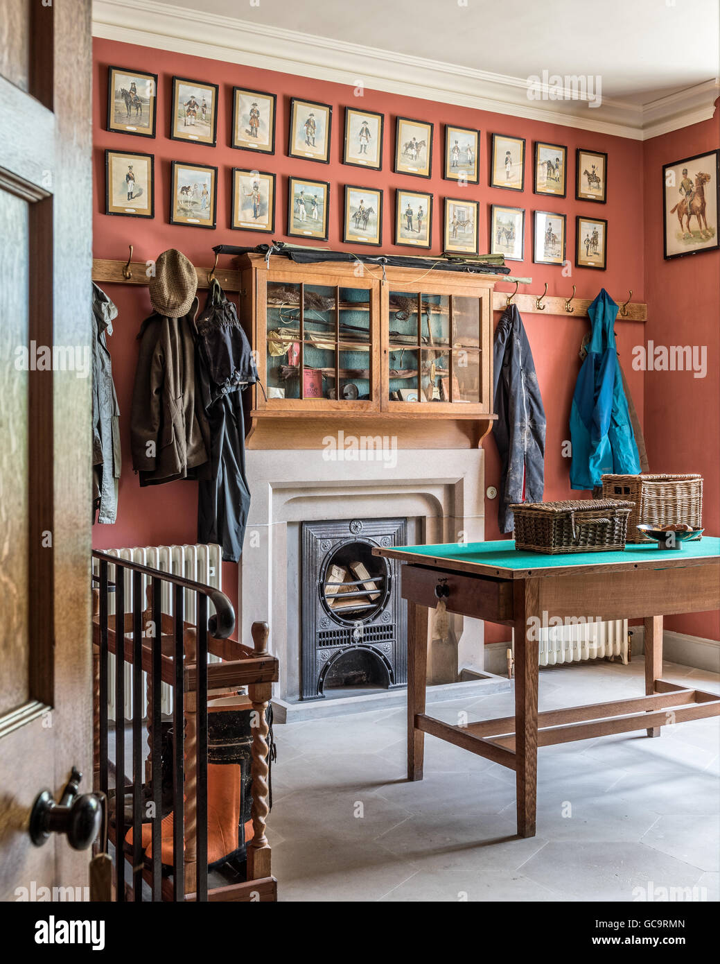Framed military uniform prints line the wall above a former gun cupboard in an old gun room with coat hooks and - Stock Image