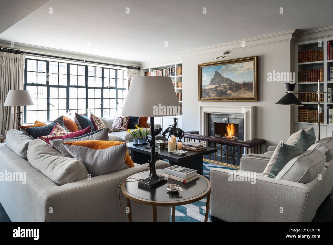 Pair of linen upholstered sofas and armchairs designed by Stephanie Everard in living room with windows - Stock Image