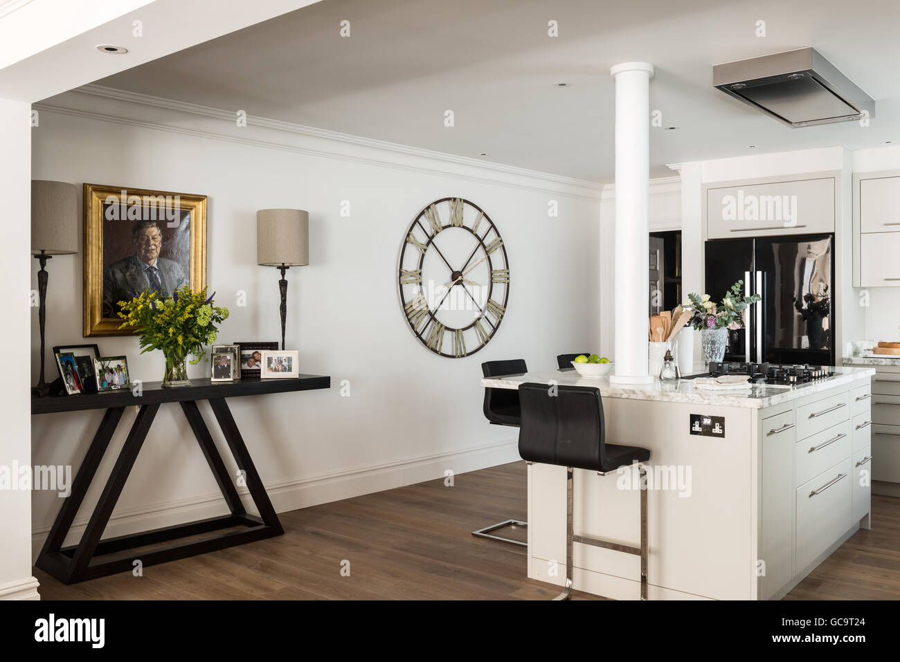 Family photos on a console table by John Chichester in open plan kitchen with large wall clock - Stock Image