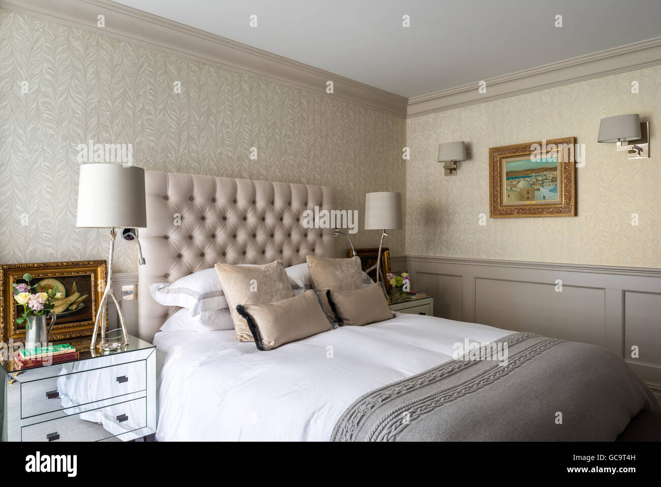 Buttoned headboard on bed flanked by mirrored drawers and lamps by Porta Romana - Stock Image
