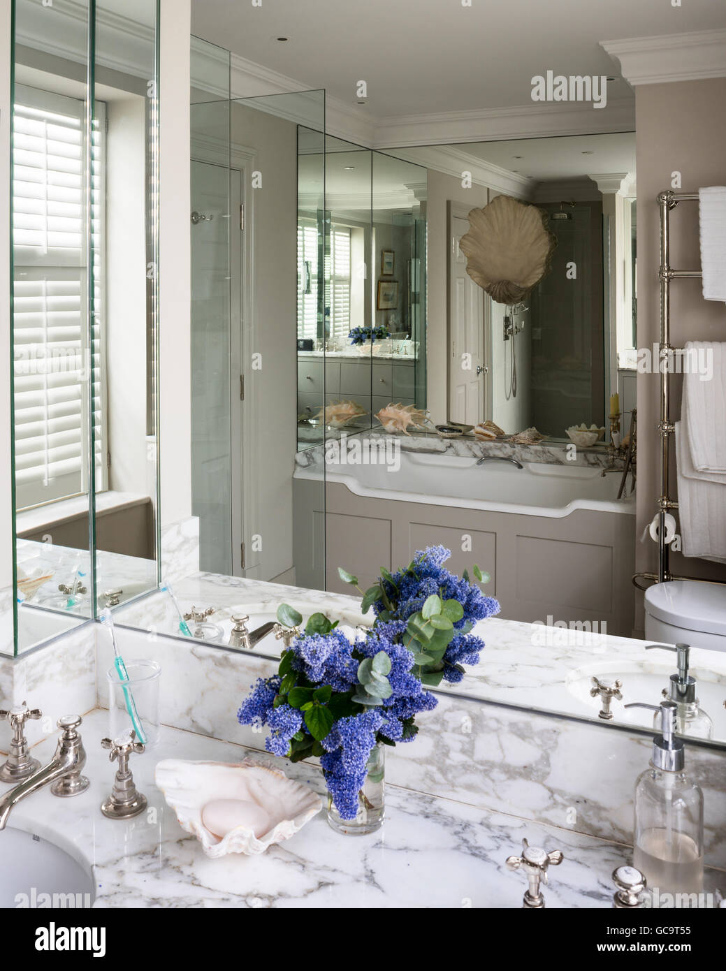 Marble vanity unit in bathroom with mirrored wall panels ...