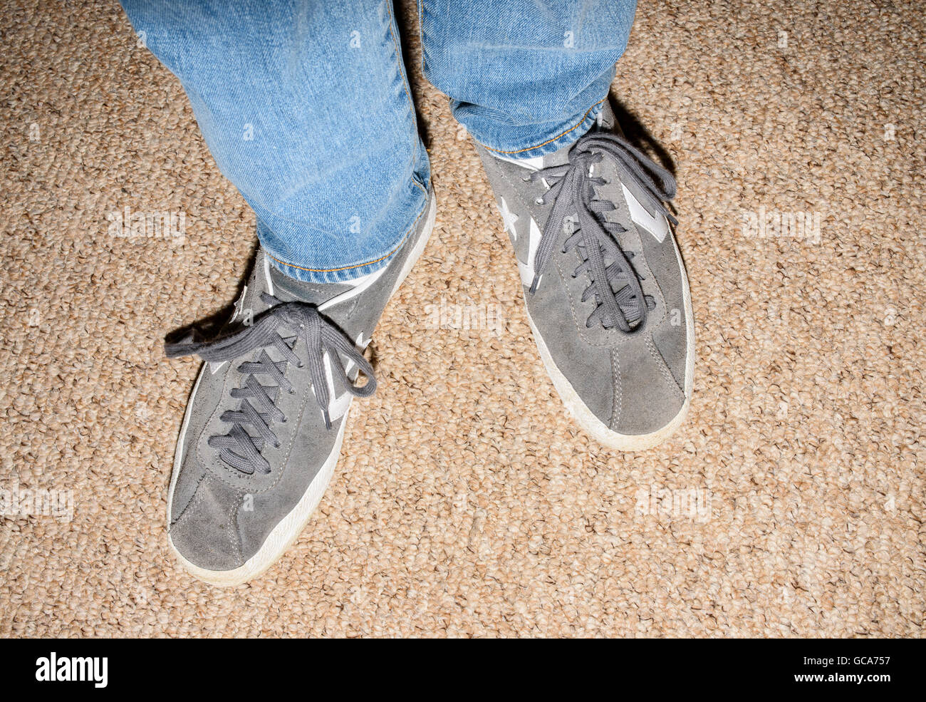 b953e6c3dcb Close up of lower legs and feet of person wearing blue denim jeans and grey  Converse