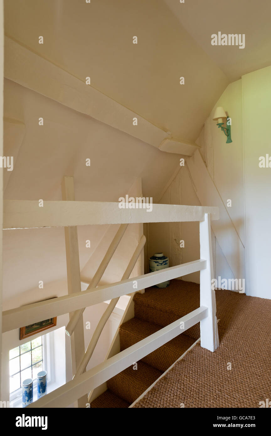 Seagrass style carpet on cottage stairwell and landing with sloped walls and ceiling - Stock Image