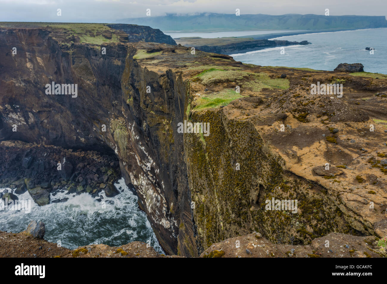 Dyrholaey promontory, formerly an island of volcanic origin with its huge arch of lava standing in the ocean. Southern - Stock Image