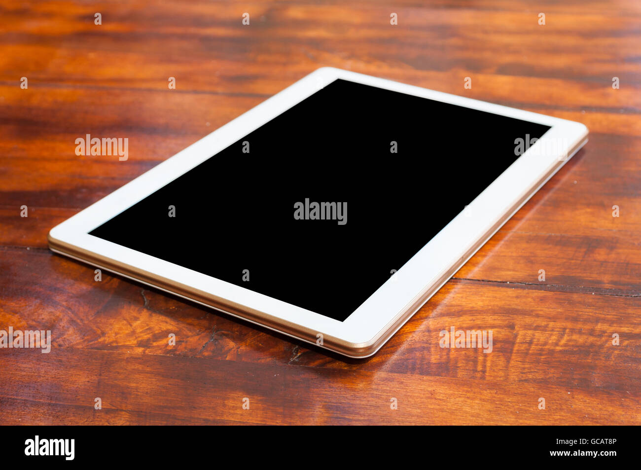 Tablet gadget on wooden terrace table with black screen with copy text space - Stock Image