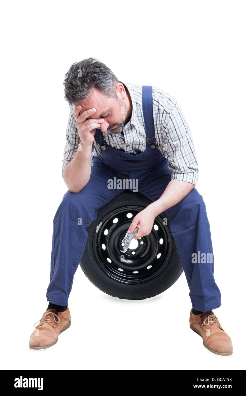 Stressful job concept with exhausted mechanic in overallas holding steel wrench isolated on white - Stock Image