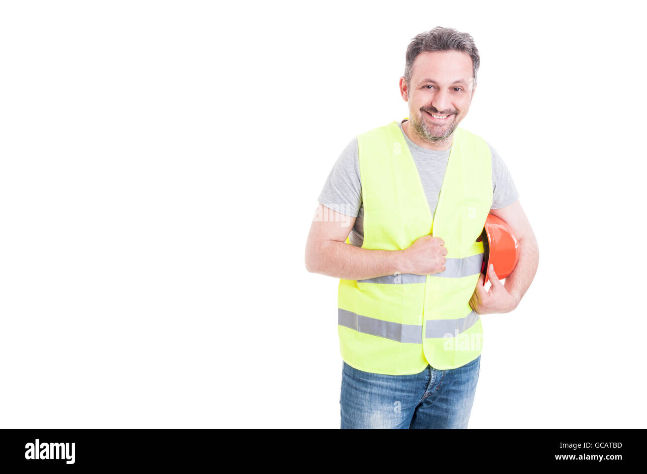 Cheerful male constructor with yellow vest holding his protection helmet isolated on white background with copy - Stock Image