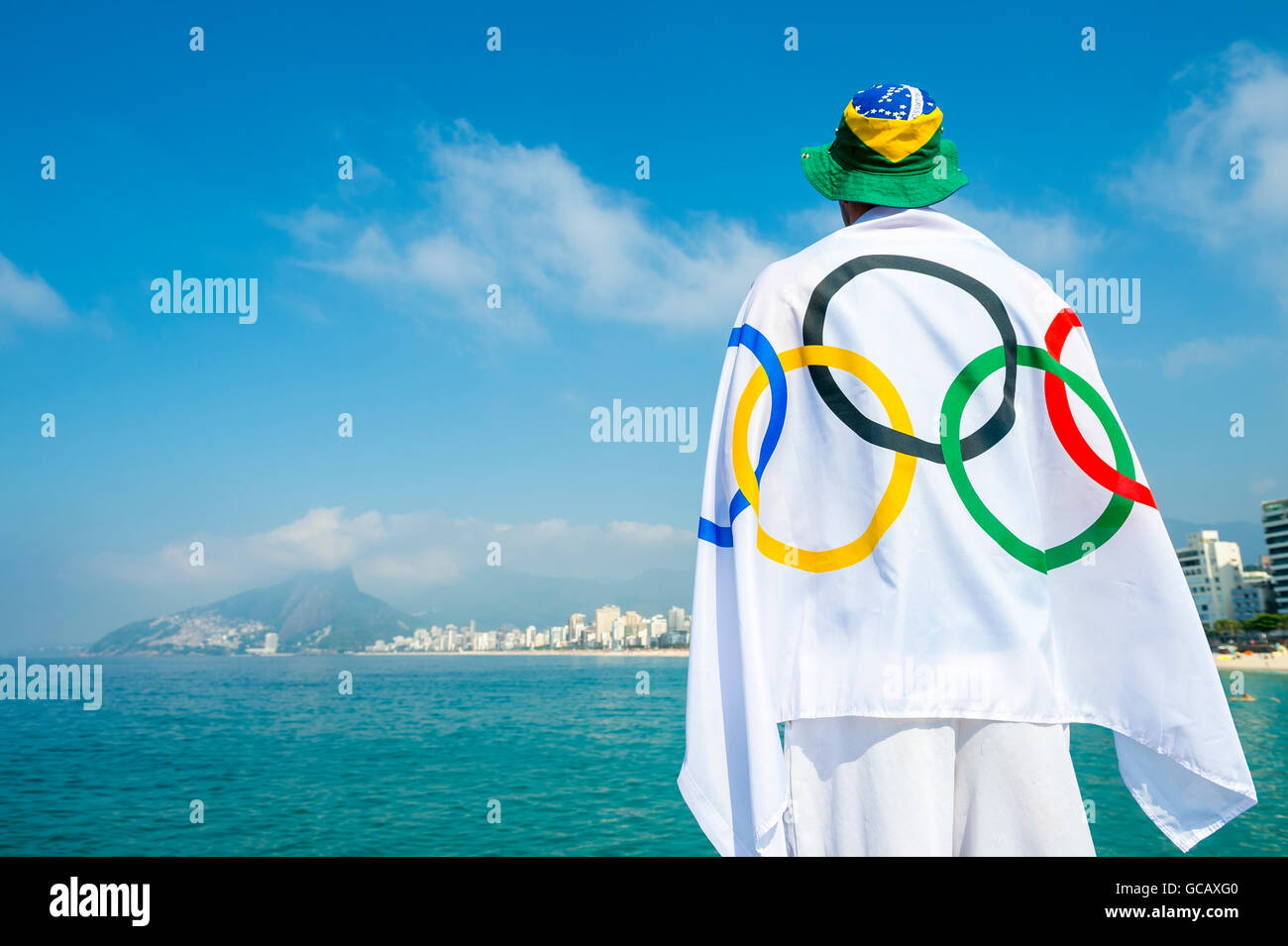 RIO DE JANEIRO - MARCH 27, 2016: Athlete draped in Olympic flag stands on the shore of Ipanema. - Stock Image