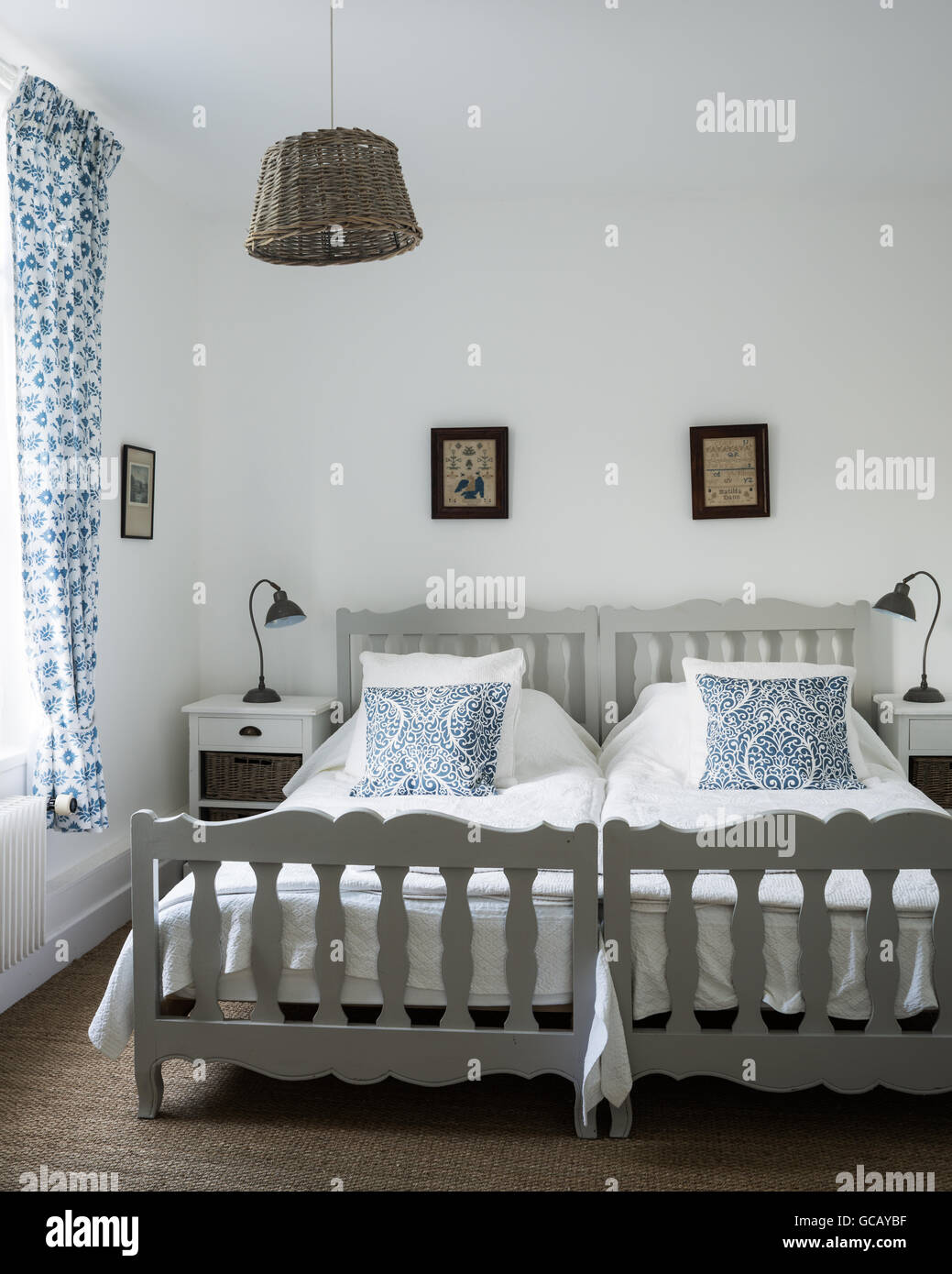 Twin Beds In Guest Room With Swedish Block Print Curtains And Basket Stock Photo Alamy
