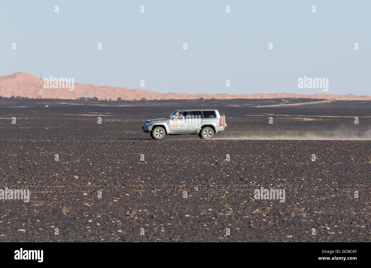 Silver Range Rover traveling in stony  Morocco desert, heading right to left, blue sky and mountains in background. - Stock Image