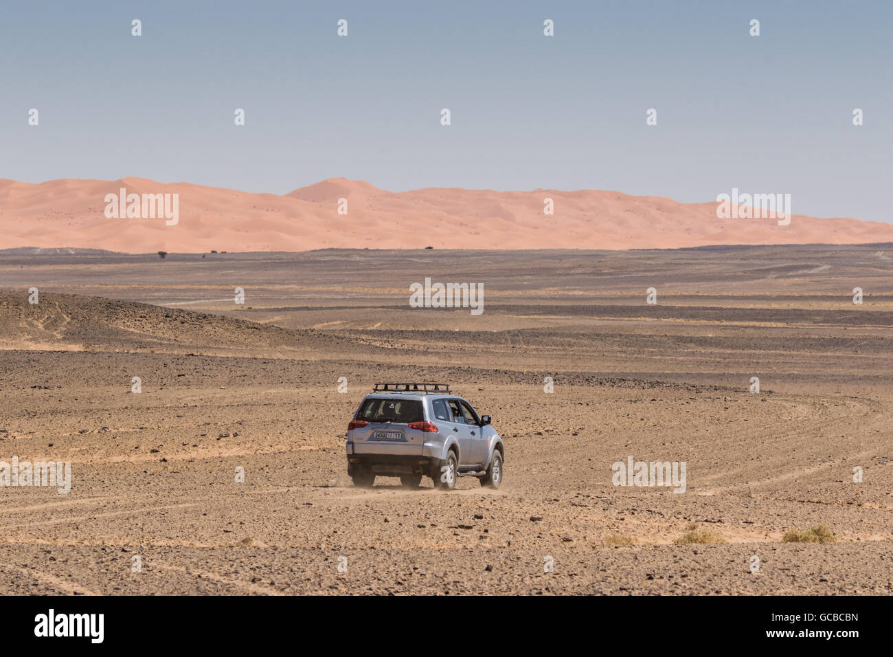 Silver Range Rover traveling into the Morocco desert, heading away from the camera towards sand dunes, blue sky - Stock Image
