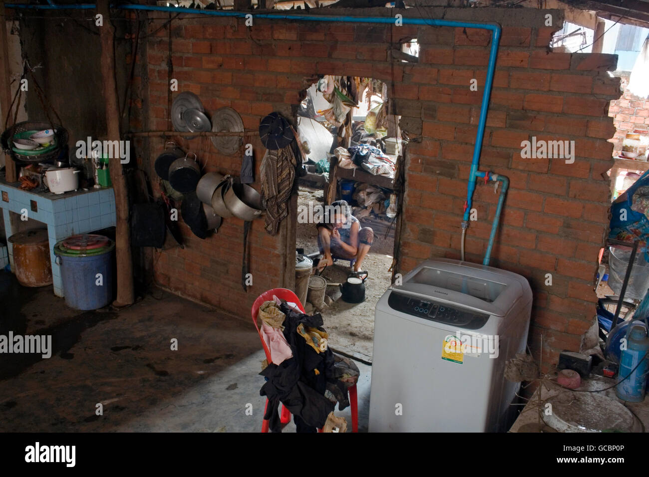 A woman is cooking near a Samsung washing machine in a messy house in Chork Village, Cambodia. - Stock Image