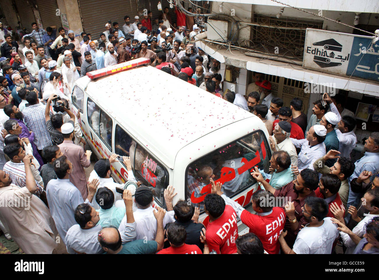 Karachi, Pakistan. 9th July, 2016. Peoples run with an ambulance carrying the coffin of Abdul Sattar Edhi, before - Stock Image
