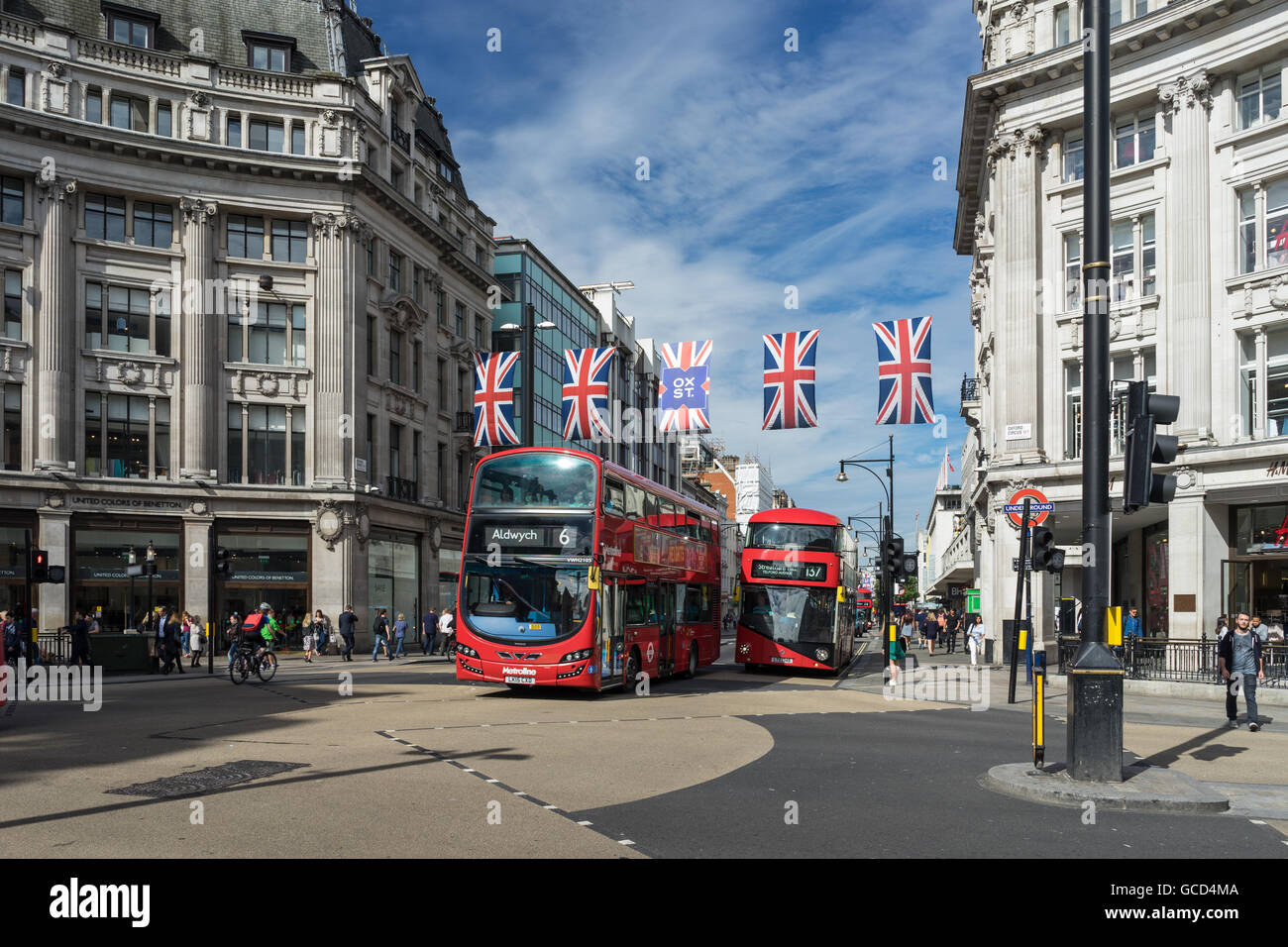 London Red Buses traveling along Oxford Street outdoors on a bright sunny day in City with commuters and traffic - Stock Image