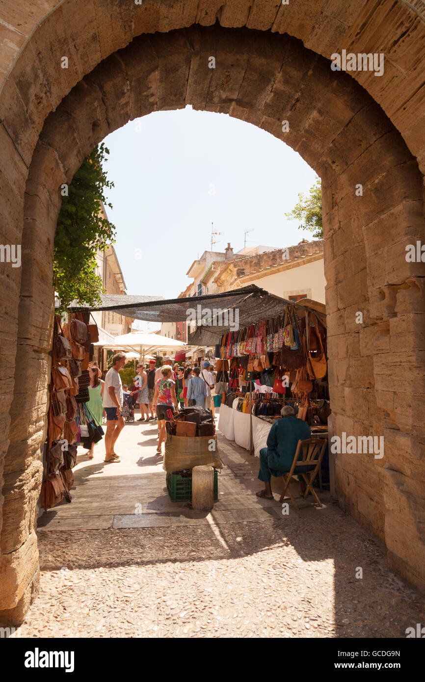 The market in Alcudia old town seen through an arch in the town walls, Alcudia old town, Mallorca ( Majorca ), Balearic - Stock Image