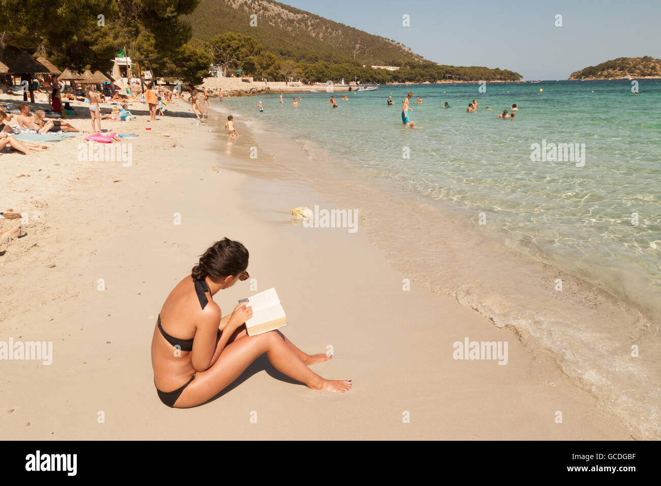 Young woman reading a book sitting on the beach, Majorca ( Mallorca ),Spain Europe - Stock Image