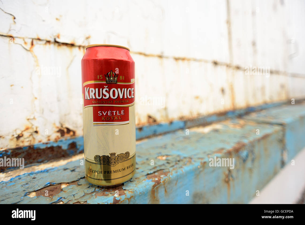 Unopened can of Krusovice 1581 Svetle Royal beer with a rusty metal background in blue and white - Stock Image