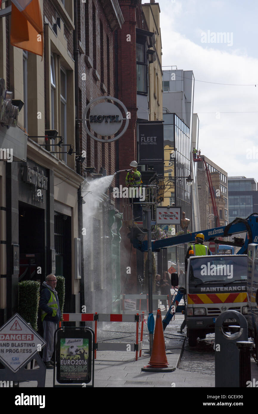 Pressure washing outside walls of a building in Dublin city - Stock Image